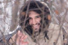 Un giovane uomo sorridente dietro l'inverno dei rami Fotografie Stock