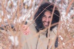 Un giovane uomo sorridente dietro l'inverno dei rami Fotografie Stock Libere da Diritti