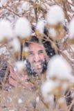 Un giovane uomo sorridente dietro l'inverno dei rami Immagini Stock Libere da Diritti