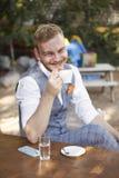 Un giovane uomo sorridente, gesto capo di cenno del capo, 20-29 anni, vestito d'uso dei pantaloni a vita bassa, sedentesi alla ta fotografie stock libere da diritti