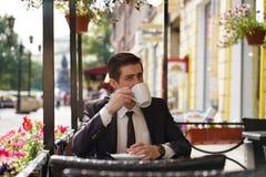 Un giovane in un vestito nero, in una camicia bianca ed in un legame sta sedendosi in un caffè della via della città ad una tavol fotografia stock