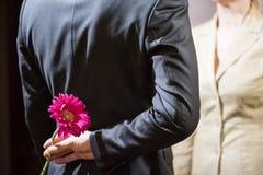 Un giovane in un vestito tiene un fiore della gerbera dietro il suo indietro, una sorpresa per una donna, l'8 marzo fotografie stock