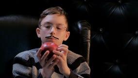 Un giovane in vetri con i baffi incollati si siede in una poltrona nera e prende una mela rossa Emozione triste sul fronte di un  video d archivio