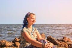 Un giovane viaggiatore bianco grassottello della ragazza con i capelli blu della treccia si siede a piedi nudi sulla sabbia contr fotografia stock libera da diritti