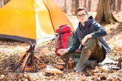 Un giovane viaggiatore nella foresta sta riposando vicino alla tenda ed alla prima colazione cucinata in natura immagini stock libere da diritti