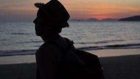 Un giovane viaggio maschio premuroso e viaggiatore con zaino e sacco a pelo calmo che guarda verso il mare e che pensa al viaggio video d archivio