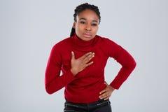 Un girlbent afroamericano un pequeño cuerpo y se aferra en su dolor de la imitación del pecho con una cara infeliz Fotografía de archivo libre de regalías
