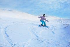 Un giro dello snowboarder da un'alta montagna nevosa sotto un cielo blu Fotografie Stock Libere da Diritti
