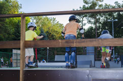 Un giro di tre adolescenti sul motorino di scossa da skatepark Fotografia Stock