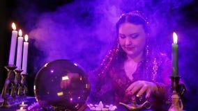 Un gitan dans une robe rouge dans la fumée par lueur d'une bougie lit l'avenir dans une boule de miroir banque de vidéos