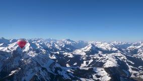 Un globo del aire caliente en vuelo sobre los picos alpinos nevados de la alta monta?a de Suiza central metrajes