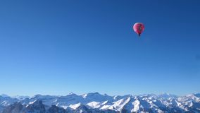 Un globo del aire caliente en vuelo sobre los picos alpinos nevados de la alta monta?a de Suiza central almacen de metraje de vídeo