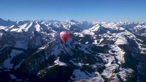 Un globo del aire caliente en vuelo sobre los picos alpinos nevados de la alta monta?a de Suiza central almacen de video