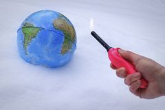 Un globo in neve con una persona che tiene un accendino con una fiamma, concetto per riscaldamento globale immagini stock