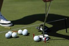 Un golfeur avec la mise et boules près d'un hall image stock