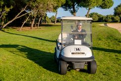 Un golfeur conduit un chariot de golf sur un terrain de golf photo stock