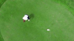Un golfeur joue sur un cours, frappant une boule banque de vidéos