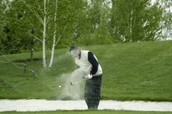 Un golfista bate hacia fuera una bola Imagenes de archivo