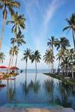 Un golfo tailandés, paraguas rojos, camas del tablón y una palma Fotografía de archivo