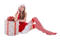 Un gomito di seduta della ragazza su un regalo su un bianco ha isolato il fondo Immagini Stock