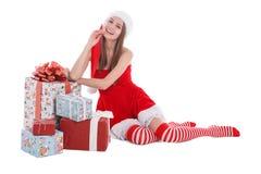 Un gomito di seduta della ragazza sui regali su un bianco ha isolato il fondo Fotografia Stock Libera da Diritti