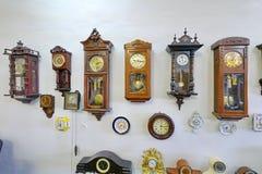 Un gran número de dispositivos totalmente diversos del reloj está situado en una pared Fotos de archivo libres de regalías