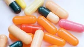 Un gran número de píldoras que caen en la opinión superior del fondo blanco en la cámara lenta metrajes