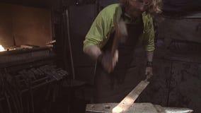 Un gran plan de un herrero en el trabajo El herrero saca un objeto candente y comienza a forjarlo en el yunque Muy cinemático metrajes