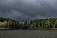 Un grand étang de forêt conifére foncée avec les nuages foncés et terrifiants Photographie stock libre de droits
