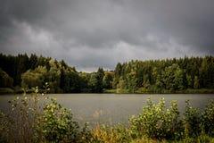 Un grand étang et une forêt conifére dense à l'arrière-plan avant la tempête Photos stock