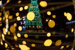 Un grand arbre de Noël avec les guirlandes lumineuses et l'étoile brillent le duvet léger sur la rue en hiver Décoration de la vi Photos libres de droits