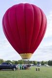 Un grand ballon à air d'un rouge ardent juste au-dessus de la terre Photos stock