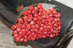 Un grand bouquet de belles fleurs roses et blanches se trouve sur le sofa en cuir Images stock