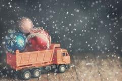 Un grand camion à benne basculante porte des boules de Noël pendant des tempêtes de neige et les chutes de neige images libres de droits
