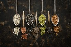 Un grand choix de graines dans des cuillères, chia, lin, potiron, tournesol, coriandre, sésame, sésame noir sur un fond foncé Vue images libres de droits