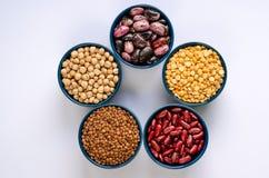 Un grand choix de l?gumineuses Lentilles, pois chiches, pois et haricots dans des cuvettes bleues sur un fond blanc Vue sup?rieur image stock