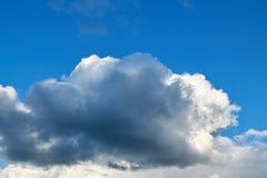 Un grand cumulus foncé obscurcit le ciel bleu clair photographie stock libre de droits