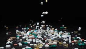 Un grand et divers assortiment des drogues pharmaceutiques ou des suppléments de vitamine tombent sur un fond noir clips vidéos