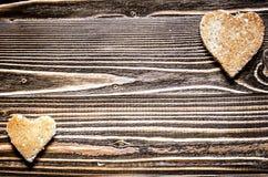Un grand et peu de coeur de pain sur une surface en bois de brun Photos stock