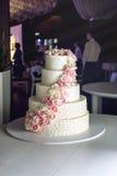 Un grand gâteau de mariage à gradins décoré des roses roses sur la table dans le restaurant Image stock