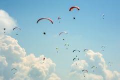 Un grand groupe de parapentistes vole dans le ciel dans la perspective des nuages Image stock