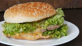 Un grand hamburger juteux délicieux avec la côtelette triple, la feuille fraîche de laitue et le fromage se trouve d'un plat blan banque de vidéos