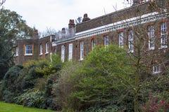 Un grand immeuble de brique européen de style parmi les buissons et les arbres verts photos stock