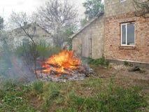 Un grand incendie brûlant près de la maison Photographie stock