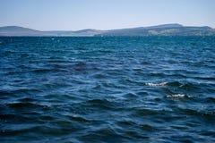 Un grand lac contre le contexte des montagnes et d'une régate de yacht dans la distance photographie stock libre de droits