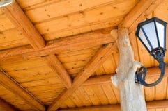 Un grand métal en verre blanc de fer a forgé le réverbère avec un plafond sur le fond d'un plafond jaune en bois fait de panneaux images stock