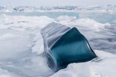 Un grand morceau carré bleu-foncé de glace sur la surface de Baikal congelé Photographie stock libre de droits