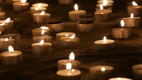 Un grand nombre de petites bougies rondes blanches brûlant dans le sable Fond des bougies brûlantes de cire banque de vidéos