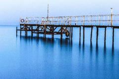 Un grand nuage de brumeux un dock vide en vent de calme de matin images stock