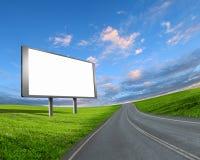 Un grand panneau d'affichage placé à la gauche de la route avec un grand ciel de perspective Image libre de droits